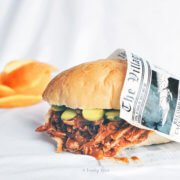 orange bbq pulled pork sandwich wrapped in newspaper with orange peels behind it