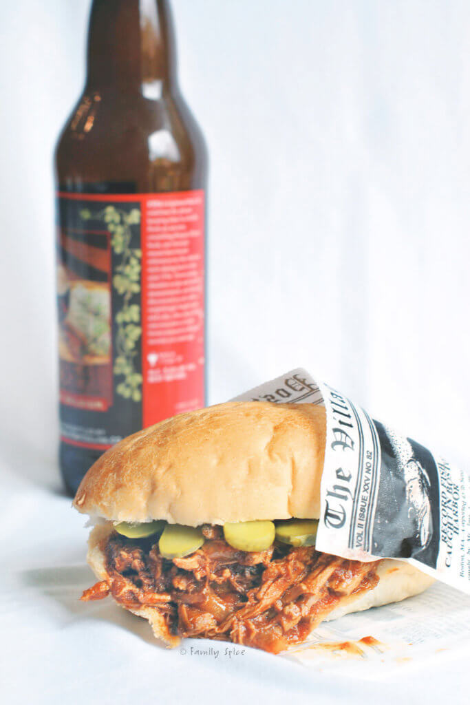 orange bbq pulled pork sandwich wrapped in newspaper with a bottle of beer behind it
