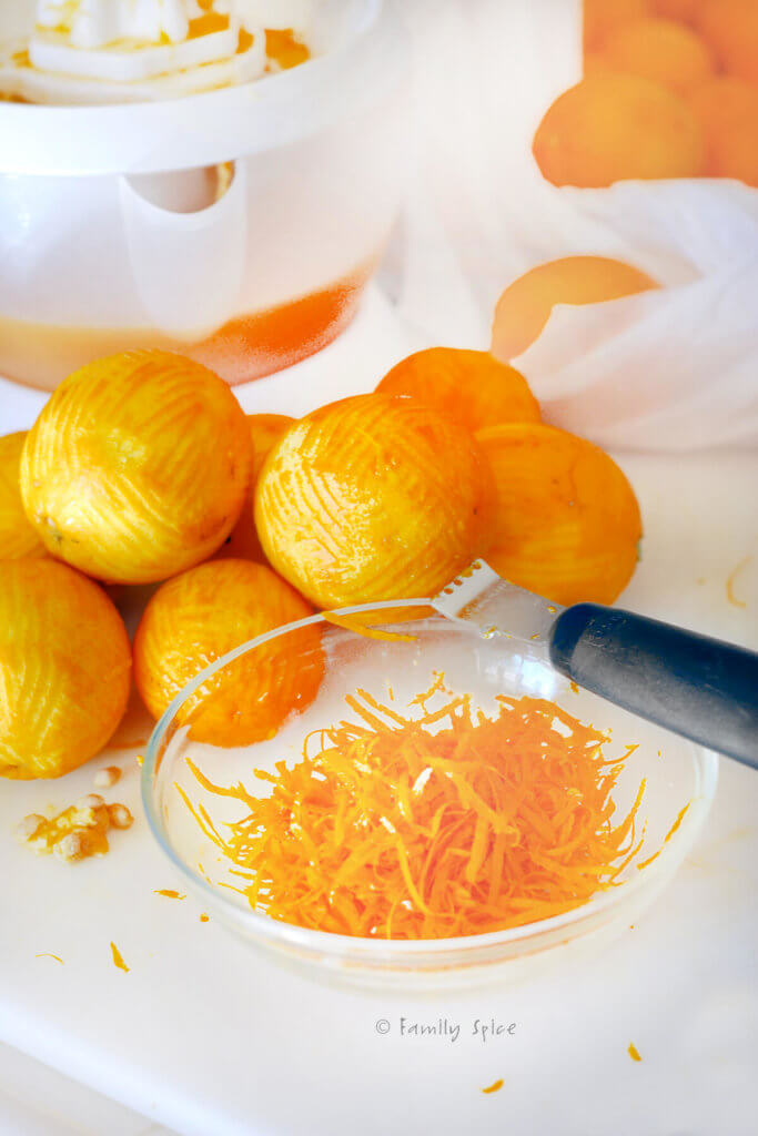 Orange zest removed from oranges and collected in a bowl with a zester