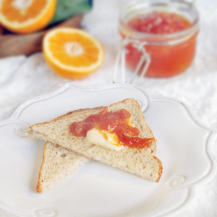 Orange jam spread on toast with a jar of orange marmalade and oranges behind it