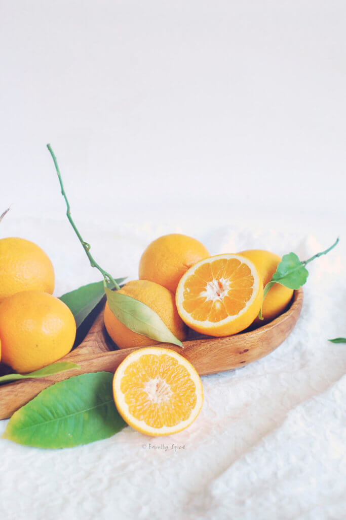 Valencia oranges, one of them halved, in a wooden bowl on a white background