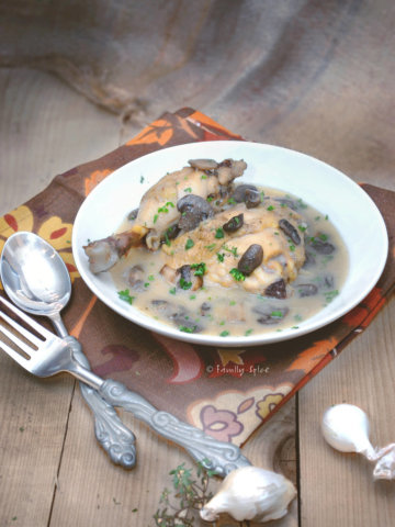 A bowl of chicken fricasse on a brown rustic background