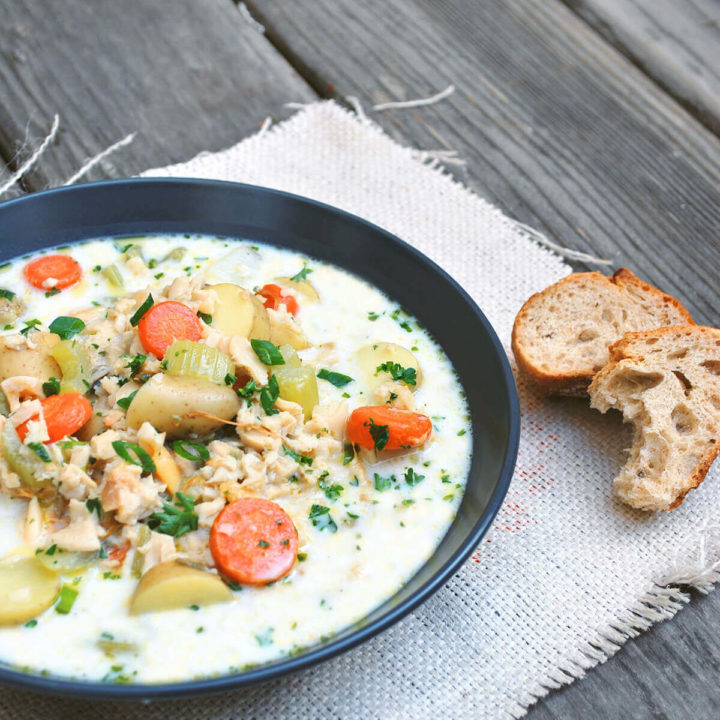 A bowl of chunky clam chowder with bread on the side
