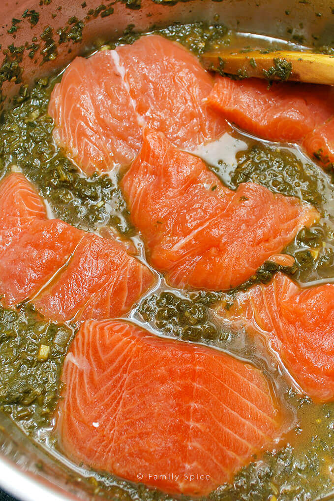 Adding salmon filets to herb stew to make Ghalieh Mahi by FamilySpice.com