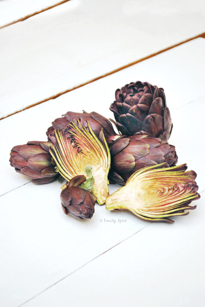 Baby purple artichokes with one cut open on a white background