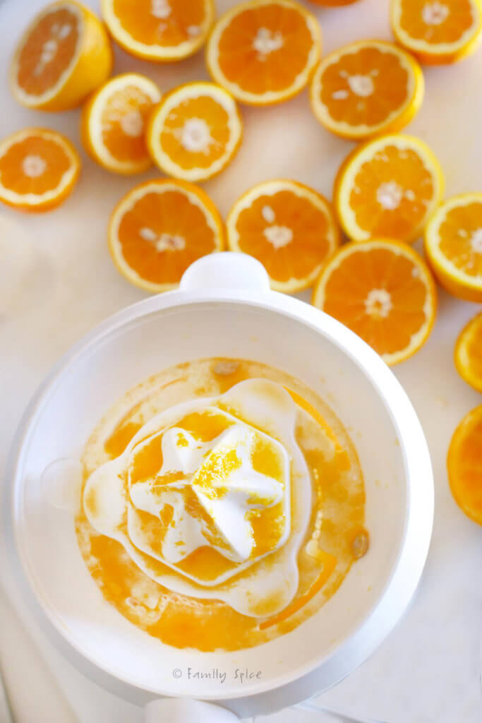 Orange halves on the counter with a juicer juicing oranges