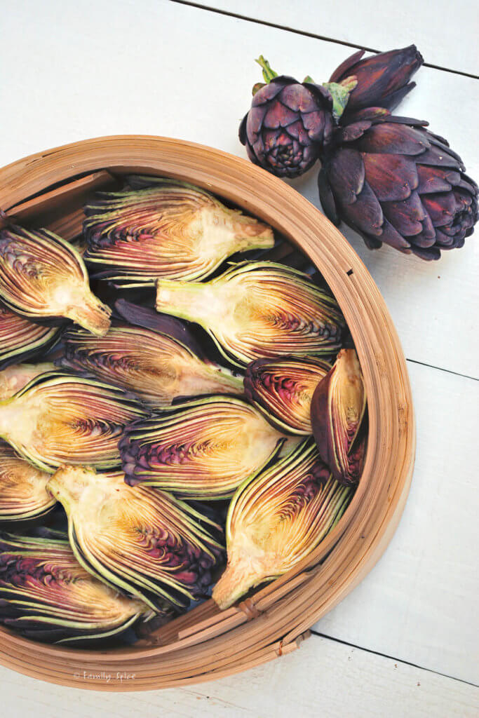 Baby purple artichokes halved and in a steamer basket