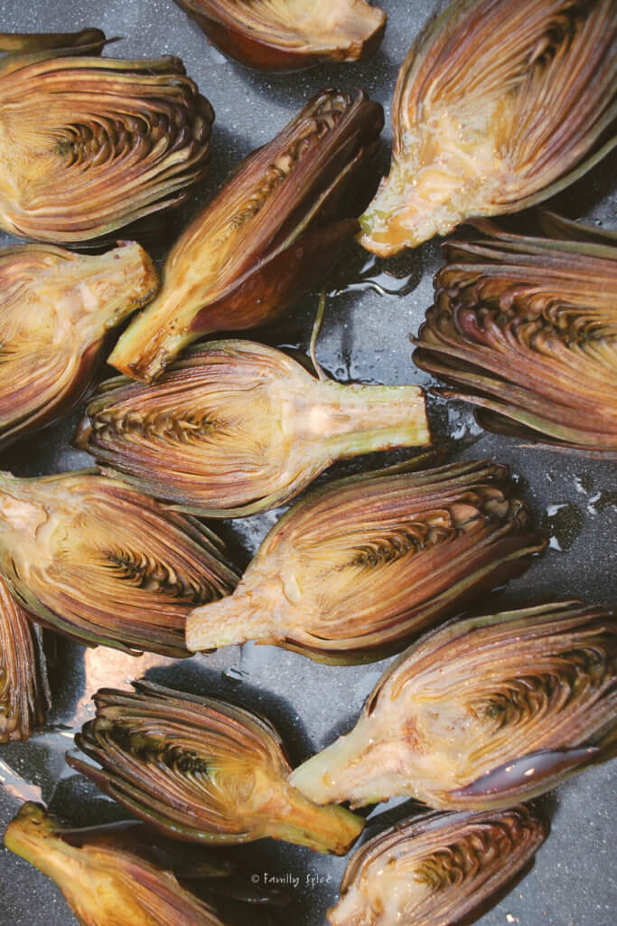 Baby purple artichokes halved and on a baking sheet