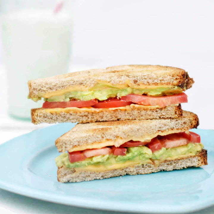 Two avocado grilled cheese halves stacked on top of each other on a blue plate