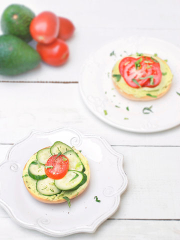 Top view of two bagels with cream cheese avocado spread with cucumbers and a tomatoes on top