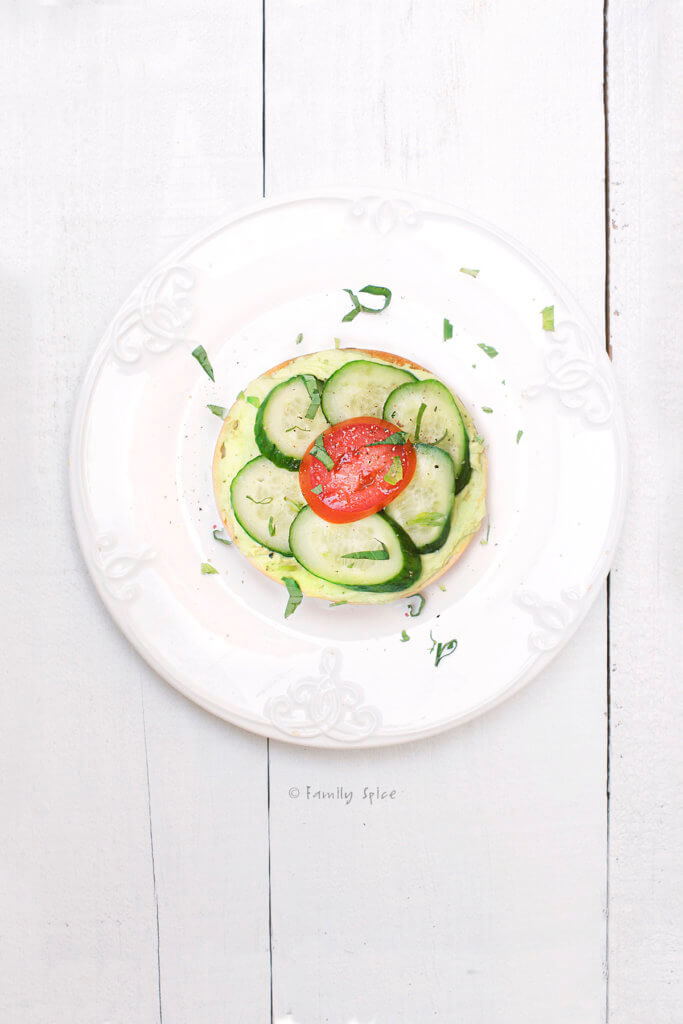 Top view of bagel with cream cheese avocado spread with cucumbers and a tomato on top