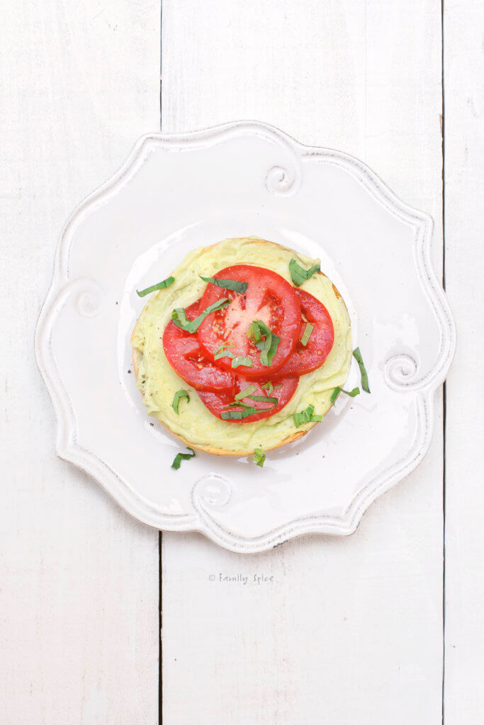 Top view of bagel with cream cheese avocado spread with tomato slices on top