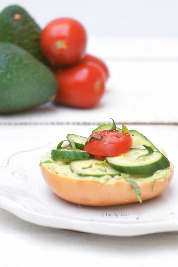 Side view of bagel with cream cheese avocado spread with cucumbers and tomatoes on top with avocados and tomatoes behind it
