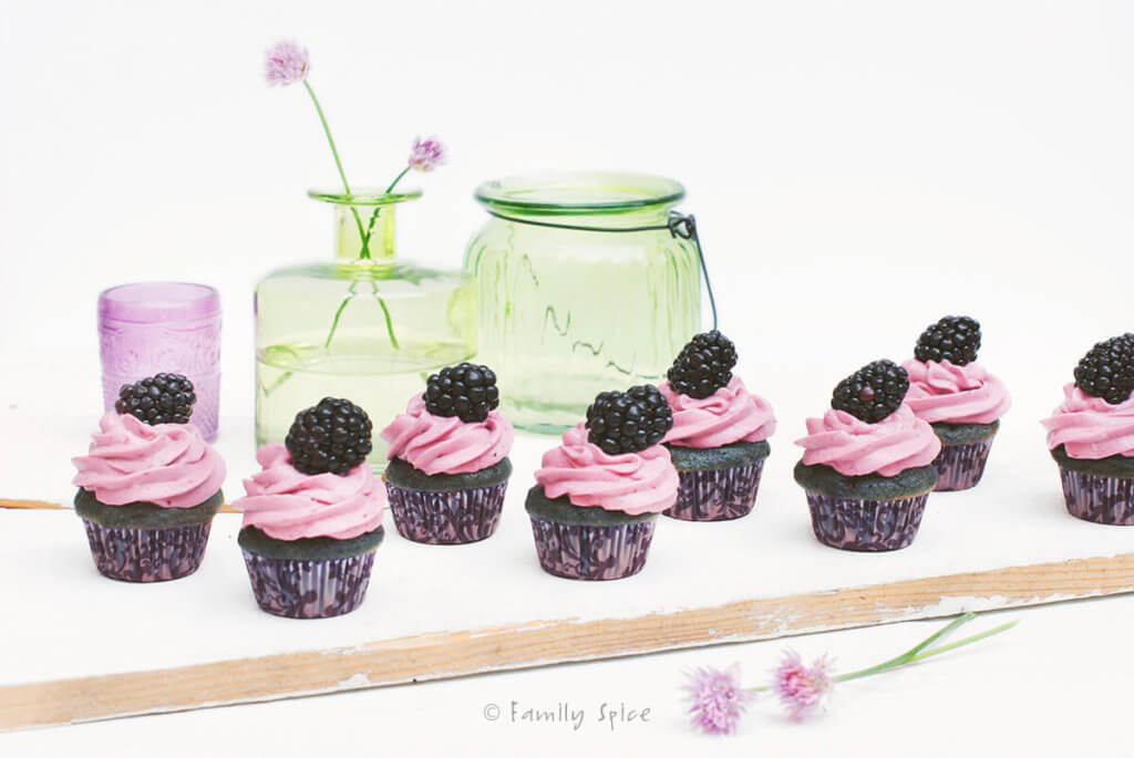 Horizontal shot of mini blackberry cupcakes on a white background with green glass bottles behind it