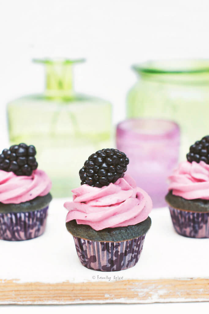 Closeup of mini blackberry cupcakes with green glass bottles behind it