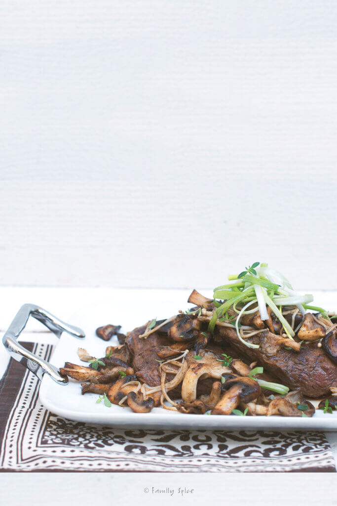Side view of a serving plate with flank steak cut into slices and served with exotic mushrooms and garnished with chive slivers
