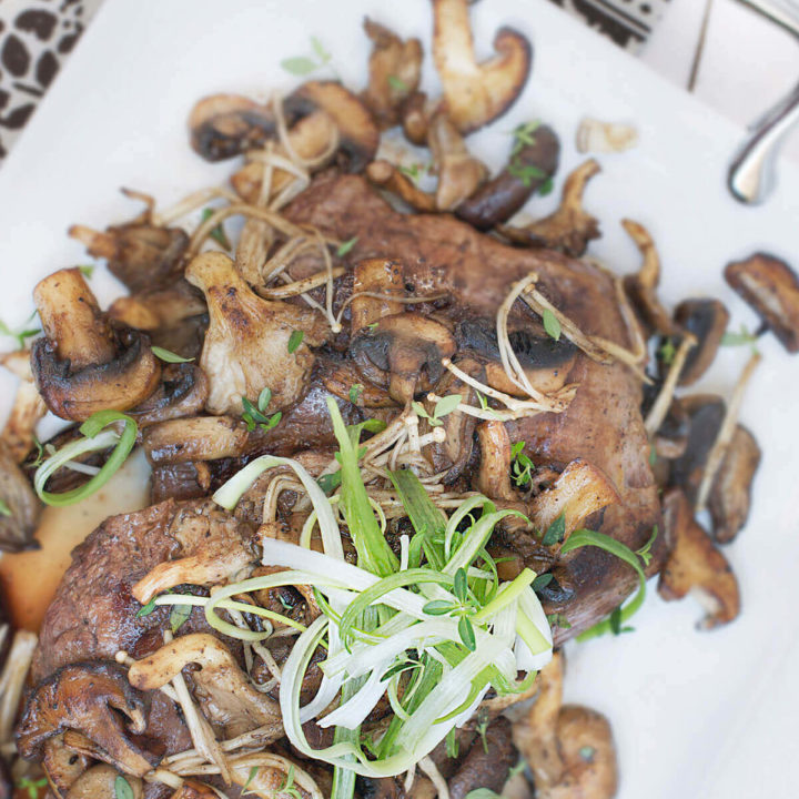 Overhead view of a serving plate with flank steak cut into slices and served with exotic mushrooms and garnished with chive slivers