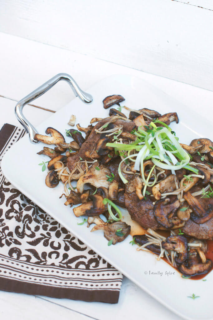 Grilled flank steak cut into slices and served with exotic mushrooms and garnished with chive slivers