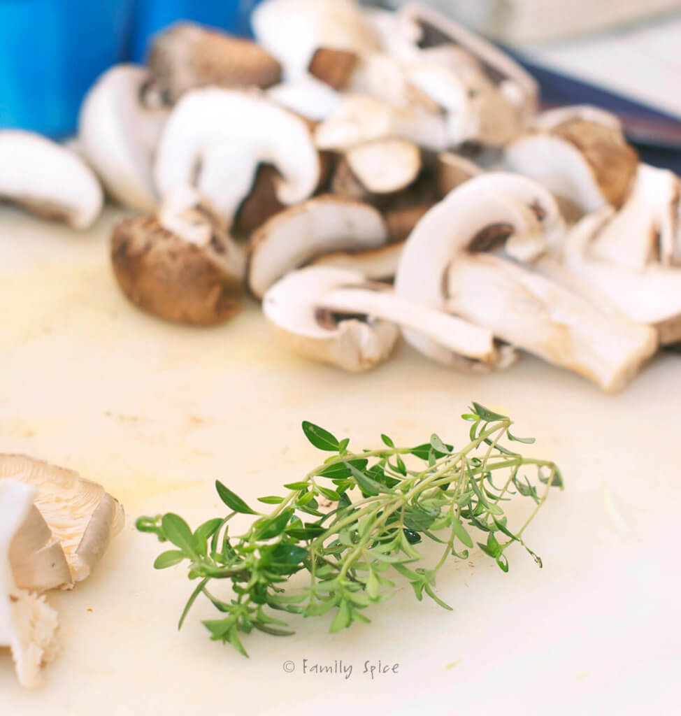 Sliced mushrooms and fresh thyme on a white cutting board