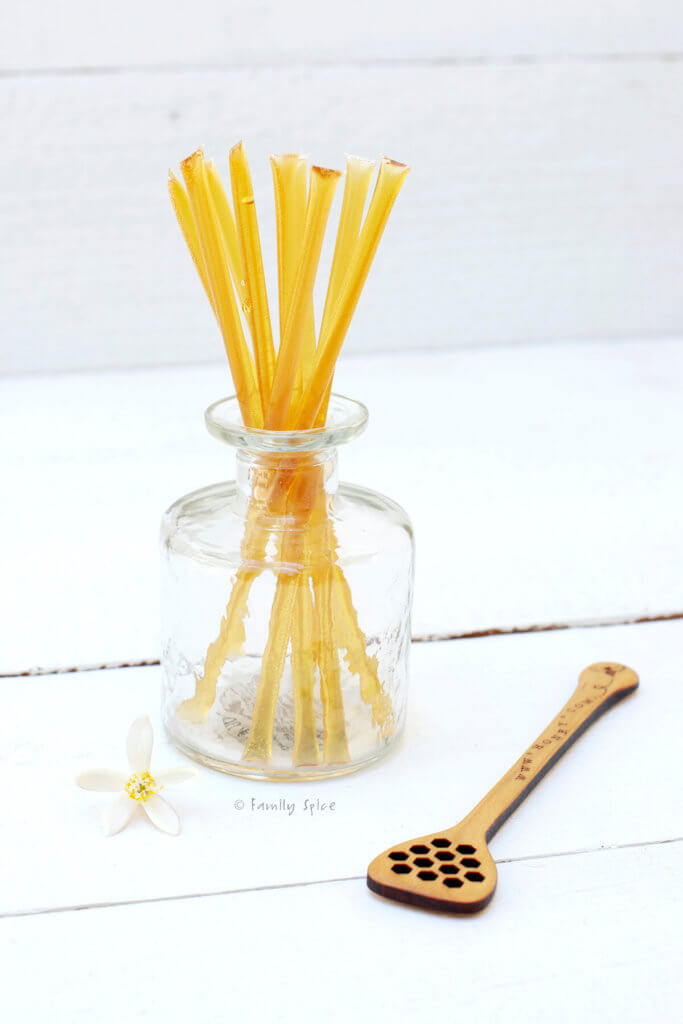 Honey sticks in a glass bottle with a wooden honey stirrer next to it