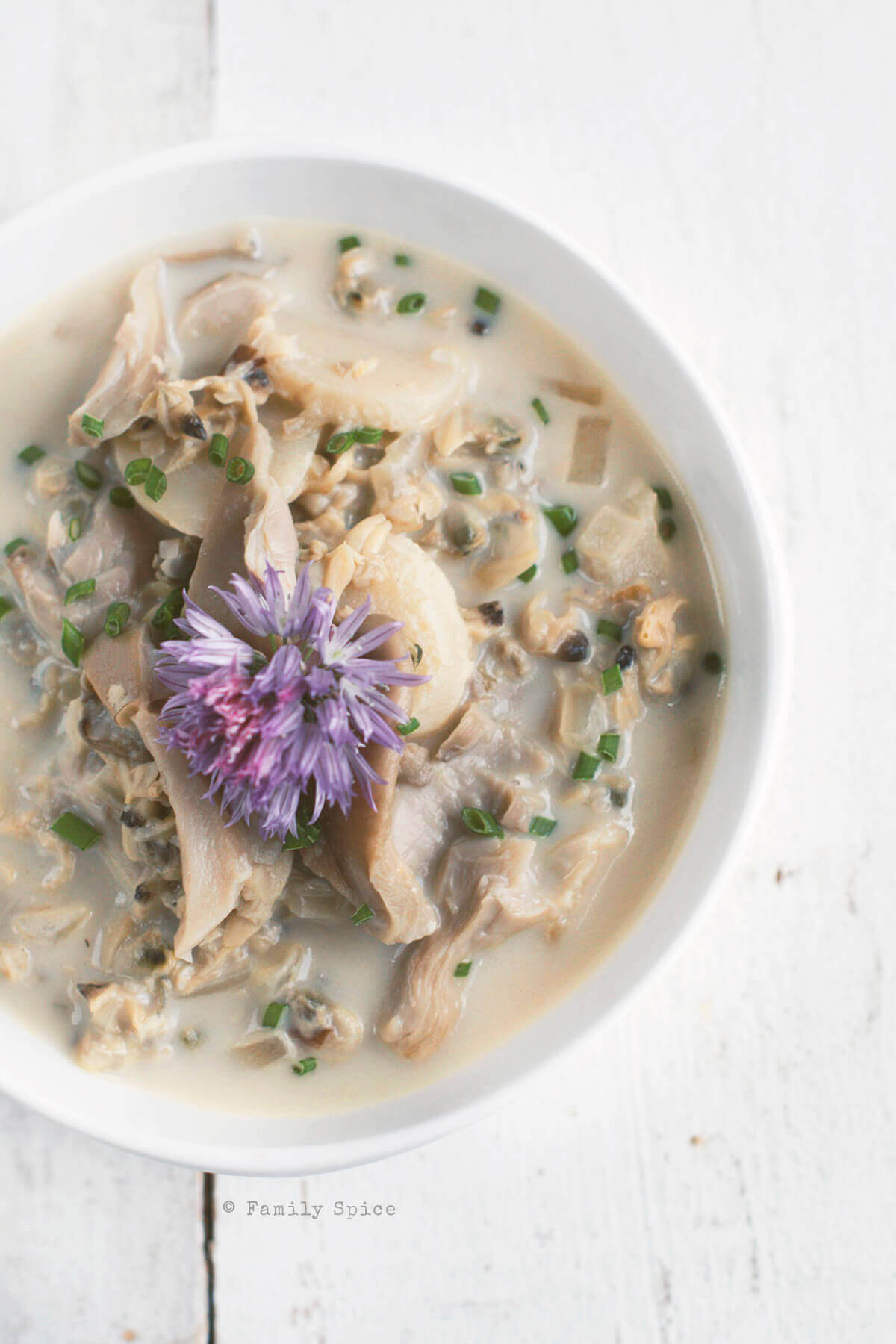 Overhead shot of a white bowl filled with asian clam chowder topped with a chive flower