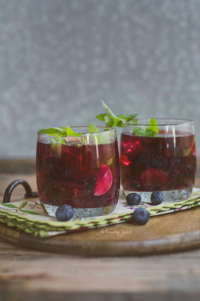 Two glasses of blueberry mojitos on a floral napkin
