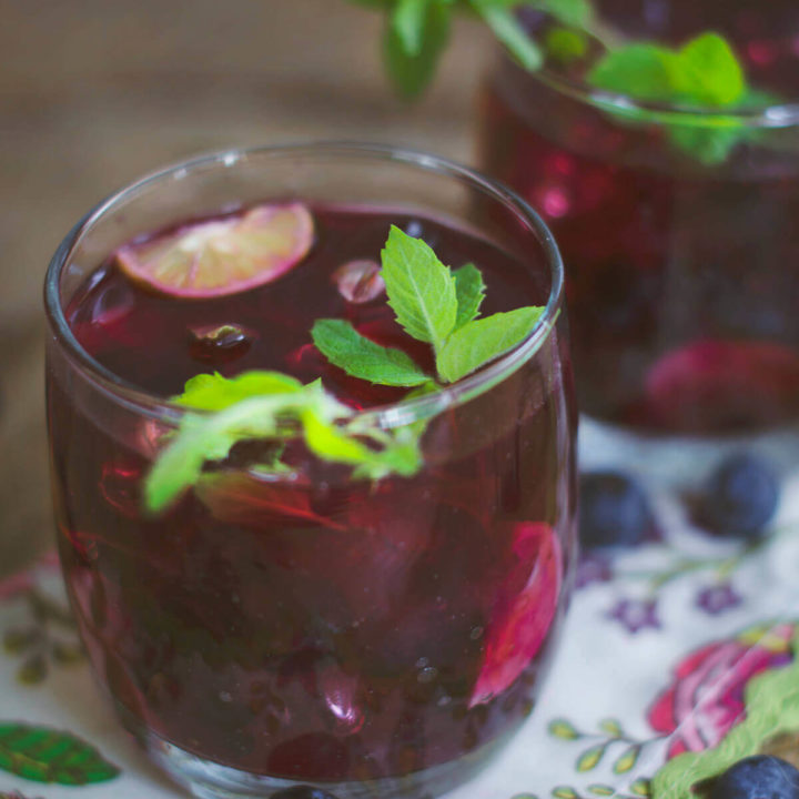 Closeup of two glasses of blueberry mojitos on a floral napkin