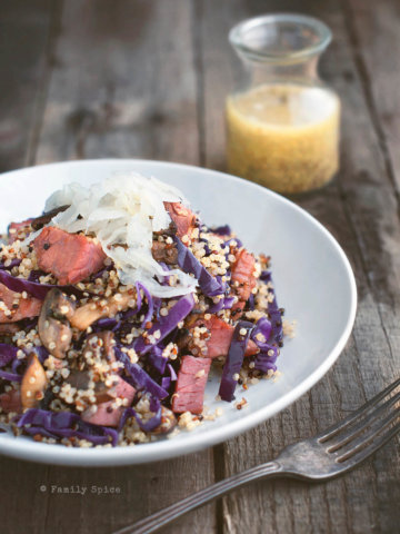 A white bowl filled with quinoa, corned beef and red cabbage topped with sauerkraut with a small bottle of mustard dressing