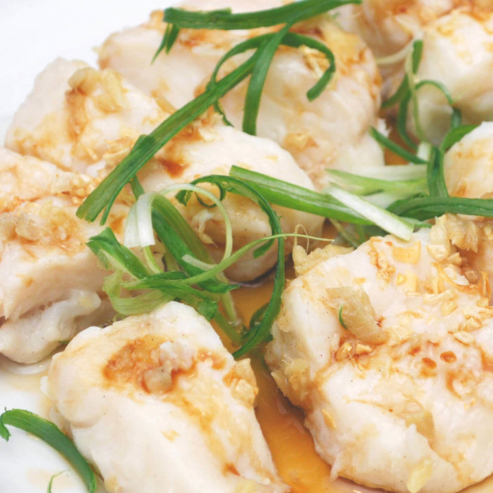 A platter of steamed halibut topped with garlic and chives