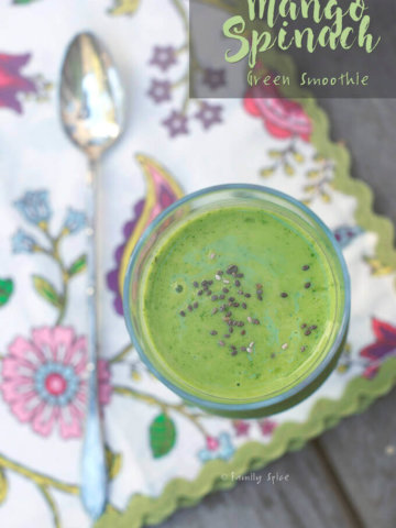 Top view of a bright green smoothie topped with chia seeds in a tall stemmed glass with floral napkin by FamilySpice.com
