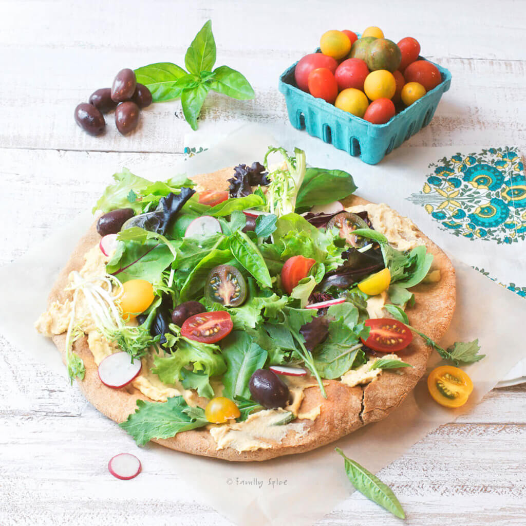 Whole wheat pizza crust topped with hummus, salad greens, tomatoes and olives with more tomatoes and olives in the background
