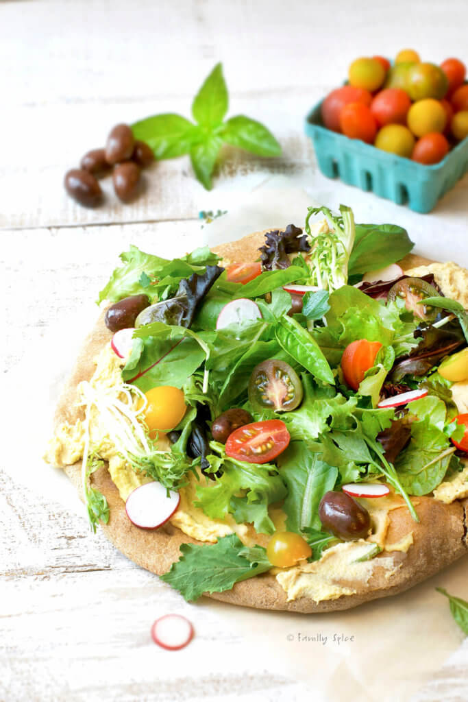 Whole wheat pizza crust topped with hummus, salad greens, tomatoes and olives