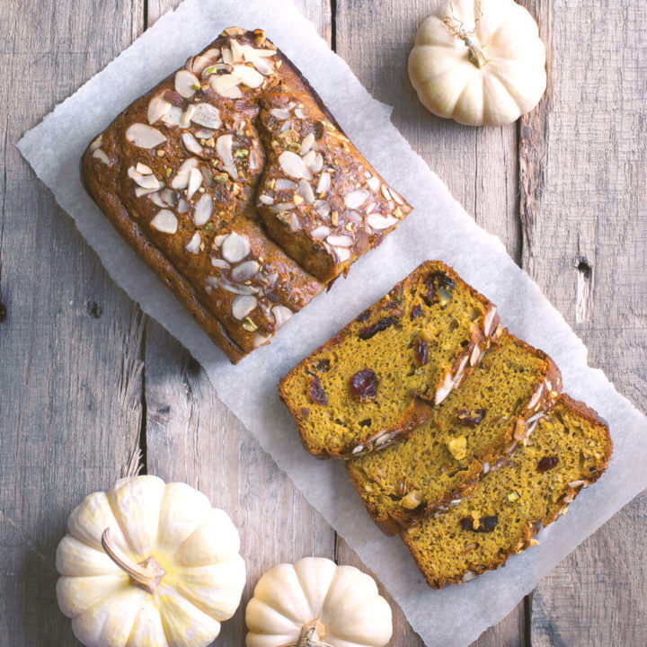 A loaf of gluten pumpkin bread on a wood table with sliced pieces and small white pumpkins around it
