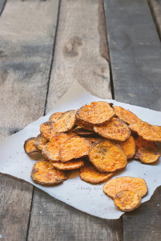 A pile of baked sweet potato chips on parchment paper and rustic wood background
