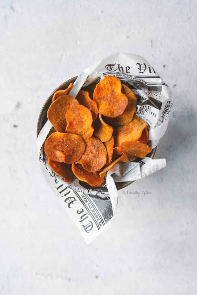 Top view of a metal container filled with baked sweet potato chips