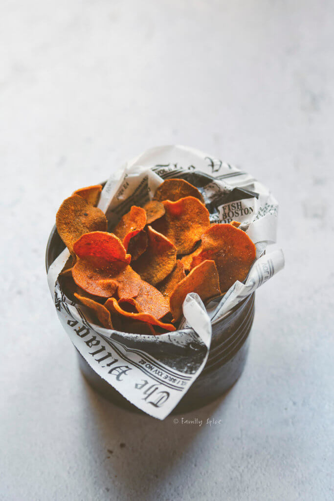Side view of a metal container filled with baked sweet potato chips