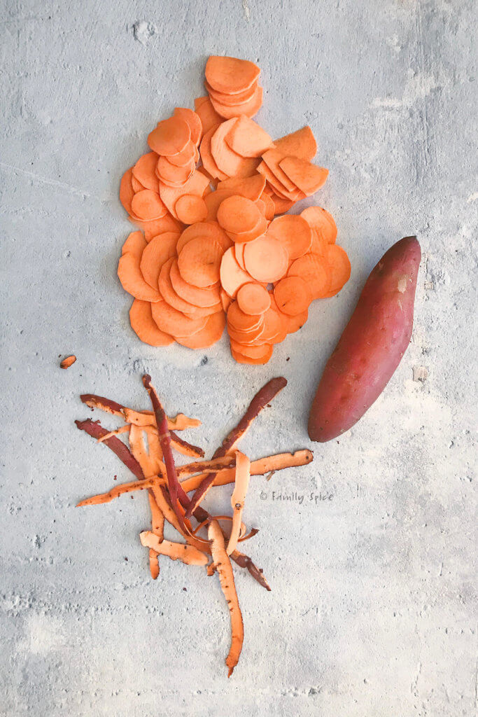 A pile of thinly sliced sweet potatoes with a whole sweet potato and some scrap peelings