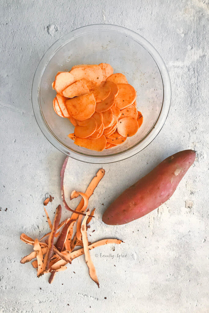 A bowl of oiled and seasoned sliced sweet potatoes with a whole sweet potato and some scrap peelings
