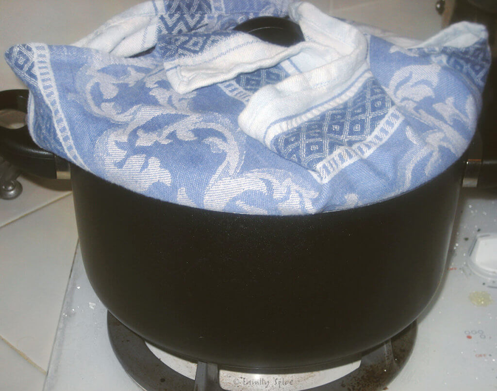 A pot on the stove with a lid covered in a towel on it