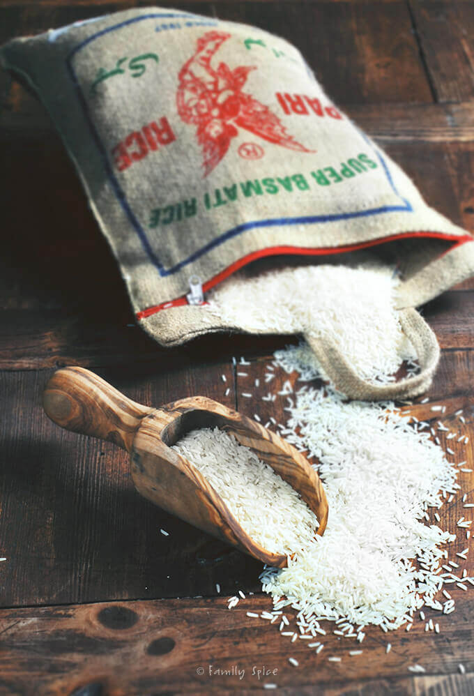 A burlap bag of long grain basmati rice spilling out of it by FamilySpice.com