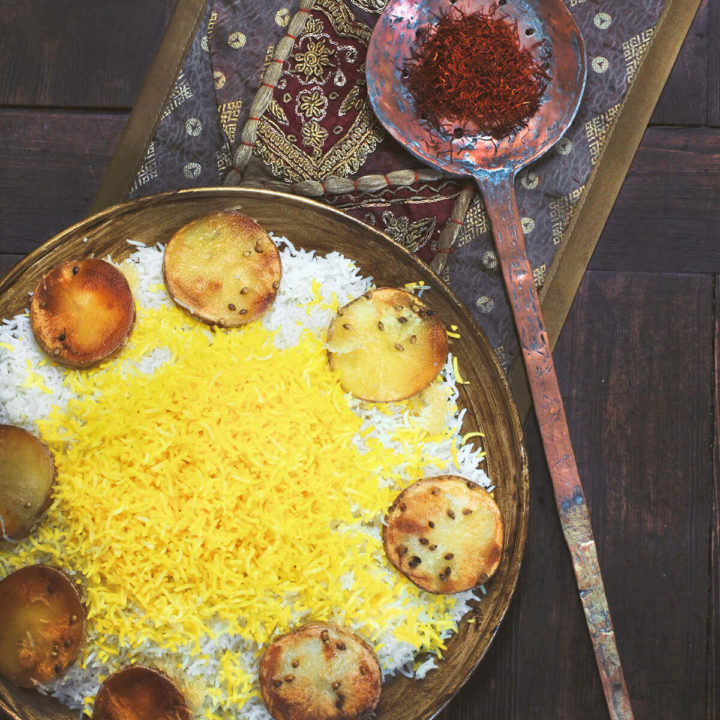 A round gold platter of Persian rice topped with saffron rice with rounds of potato tadig on a dark surface