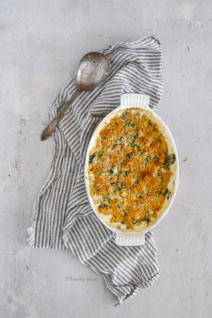 Freshly baked creamed spinach in a casserole dish with browned crushed crackers