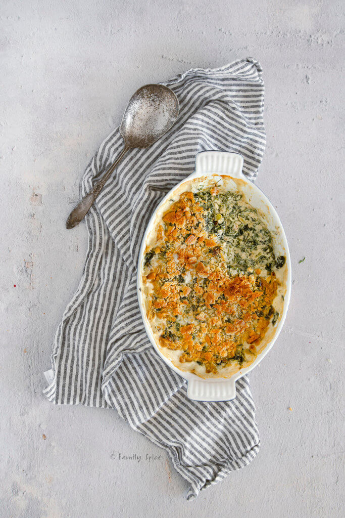 Baked creamed spinach in a casserole dish topped with browned crushed crackers and a section spooned out