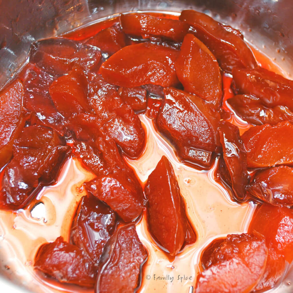 Cooking quince slices in a pot to make jam turning dark ruby red