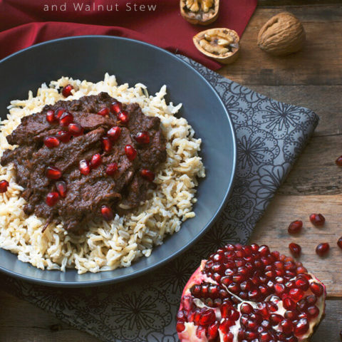 A bowl of Persian Pomegranate and Walnut Stew (Fesenjoon) over brown rice next to half a pomegranate