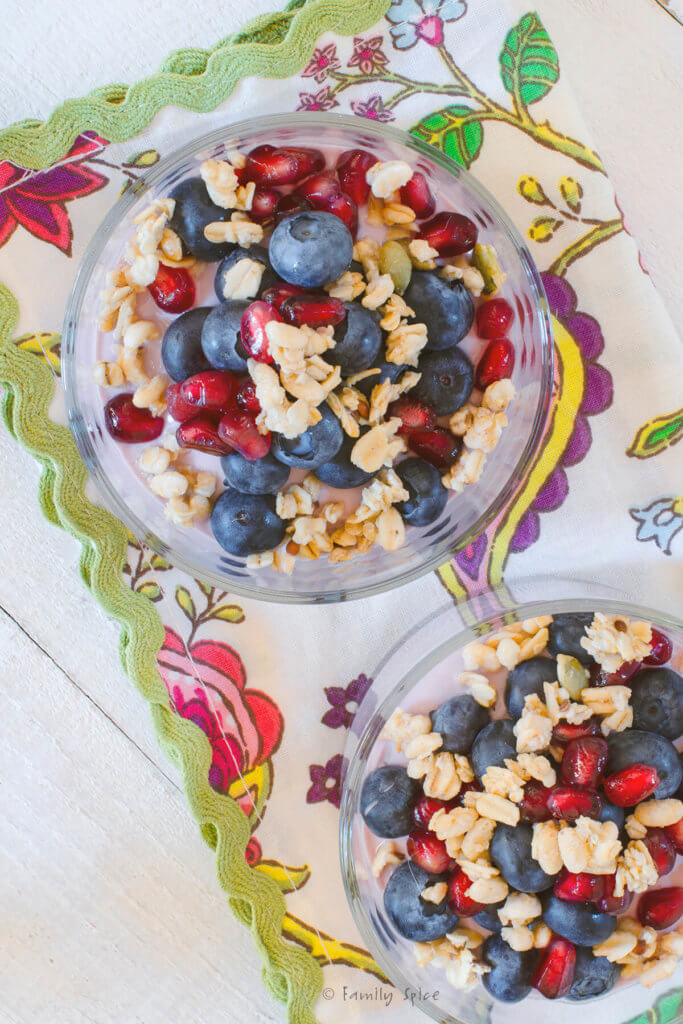 Top view of two glass bowls with pomegranate parfait topped with blueberries, pomegranate arils, walnuts and granola