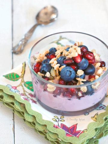 Closeup of a glass bowls with pomegranate parfait topped with blueberries, pomegranate arils, walnuts and granola