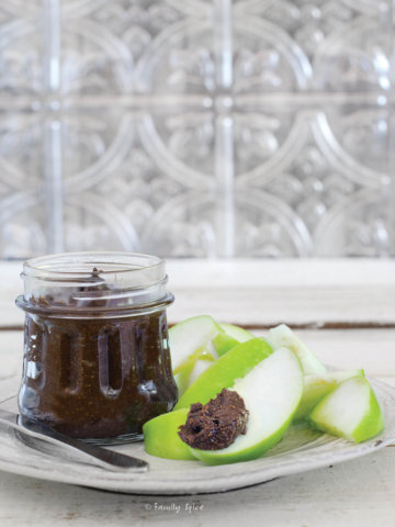Side view of a jar of carob butter with slices of green apples