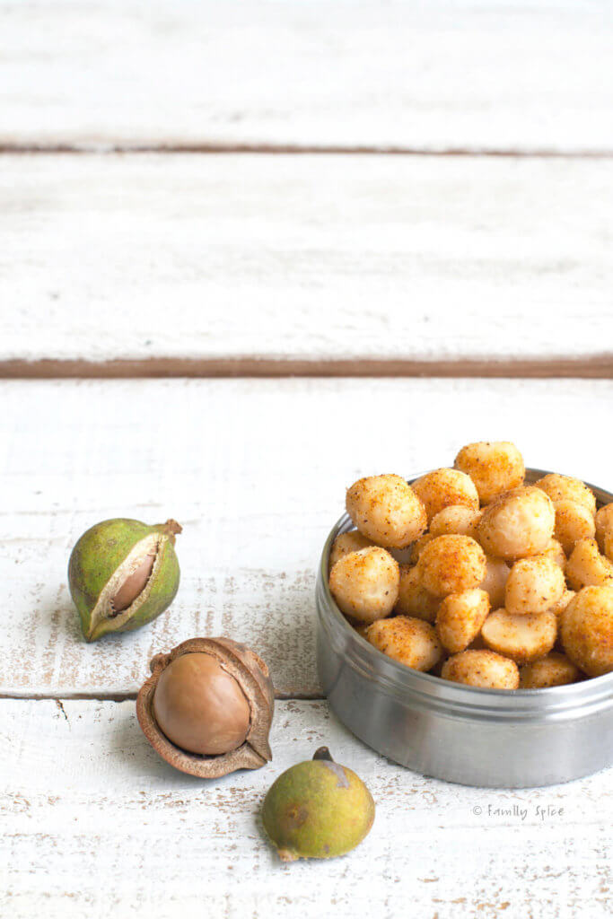 A small round metal tin with chile lime macadamia nuts in it