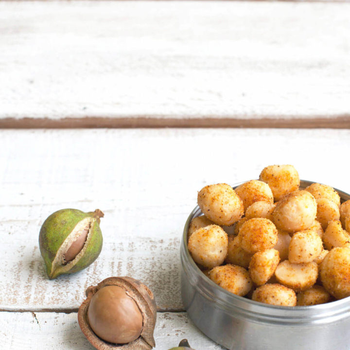 A round metal tin with chile lime seasoned macadamia nuts in it